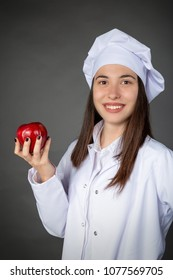 Beautiful Turkish young female chef keeping an apple on her hand