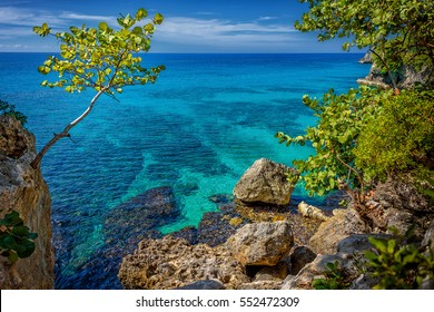 Beautiful turquoise and blue water near rocks and cliffs in Negril, Jamaica. A tree on the left and rocks on the right with a beautiful lagoon in the sea