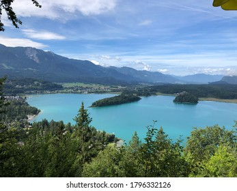 Beautiful turquoise lake in Austria with island in the middle and mountains in the back