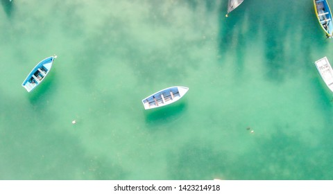 Beautiful turquoise ocean water with wooden boat on the water. Top view aerial photo.