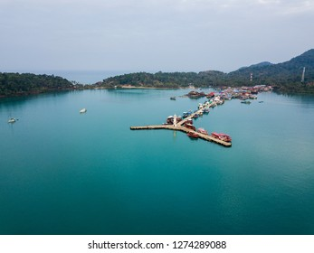 Beautiful turquoise sea with a long pier. A white ship is just mooring the other boats. Quiet, clear snapshot from the sky.