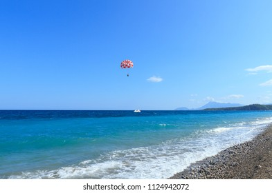 Beautiful turquoise sea and a motor boat with a parachute in Kemer, Turkey.