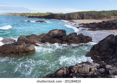 Beautiful turquoise water splashes onto jagged rocks on the shore at Clifden Bay, Connemara, Ireland.