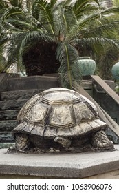 Beautiful turtle sculpture on the street of the Chinese city. Sculpture of a turtle on a background of palms