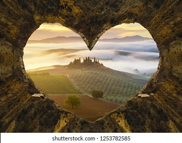 Beautiful Tuscany landscape from hearth shaped entrance of rocky cave