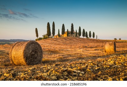 Beautiful Tuscany landscape with traditional farm house and hay bales in golden evening light, Val d'Orcia, Italy