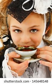Beautiful tween girl in fantasy cosplay fashion sipping tea.