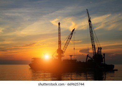 Beautiful twilight time on the sea and Cargo boat wait for load containers