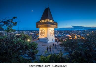 Beautiful twilight view of famous Grazer Uhrturm (clock tower) illuminated during blue hour at dusk, Graz, Styria region, Austria