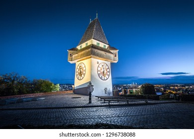 Beautiful twilight view of famous Grazer Uhrturm (clock tower) illuminated during blue hour at dusk, Graz, Styria region, Austria