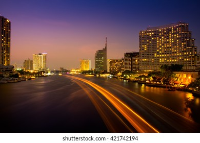 Beautiful twilightt bangkok city with speed light on chao phraya the river.