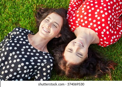 Beautiful twin sisters in red and black polka dot dresses lying on the grass close to each other and smiling