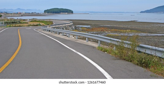 A beautiful twisty coastal road. Taken in Namhae, South Korea, but suitable to illustrate coastal life, coastal communities, twisty roads, islands, beautiful nature, traveling, or seaside living.
