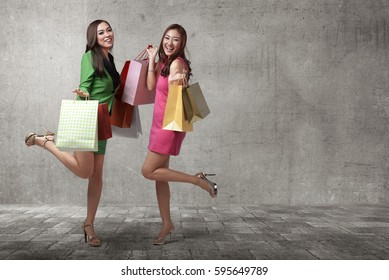 Beautiful two asian females with shopping bags walking on the urban street