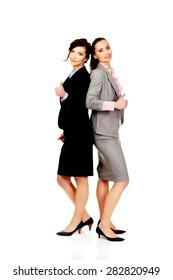 Beautiful two businesswomen showing thumbs up.