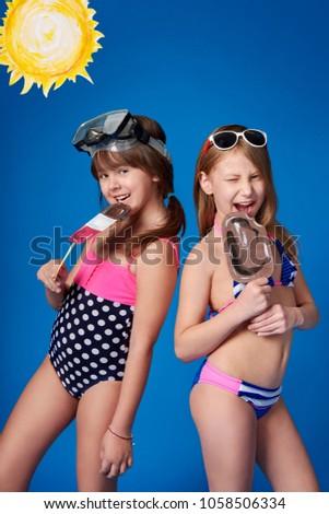38578ba133bd9 Beautiful two children girlfriend in swimwear smiling,eating ice  cream.Young cheerful girls advertise