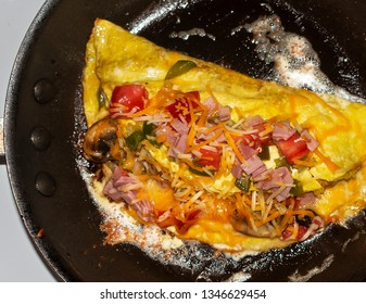 Beautiful two egg cheese omelet cooking, with diced green peppers, ham, and tomatoes, with plenty of shredded cheddar and monterrey jack cheese, in a frying pan