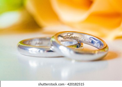 Beautiful two gold wedding rings engraved with a closeup on a background of yellow roses