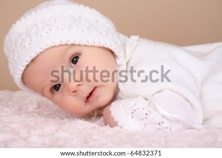 Beautiful two month old baby girl wearing a knitted outfit