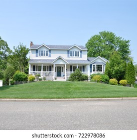 Beautiful Two Story White Suburban Home with Blue Shutters Blue Sky USA