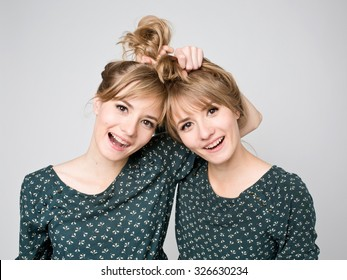 Beautiful two twins sisters together with funny hairstyle. Close-up beauty portrait