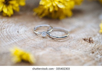 Beautiful two wedding rings, one with a diamond, on a wooden stump with some yellow Chrysanthemum flowers