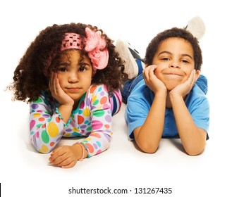 Beautiful two years old black girl with curly hair laying on white with older brother