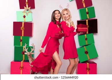 Beautiful two young women in sexy red dresses standing next to presents. Christmas glamour photo. A lot of gifts.