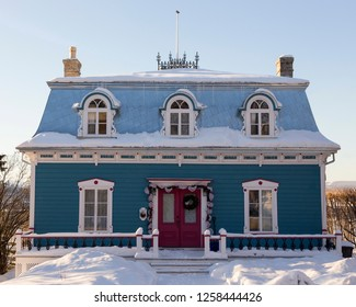 Beautiful two-chimneyed Second Empire turquoise house with metal sheet mansard roof and dormer windows seen in winter in old Lévis, Quebec, Canada