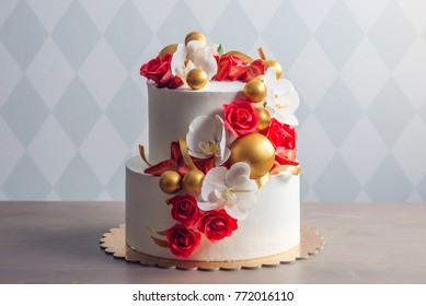 A beautiful two-tiered white wedding cake decorated with red roses and chocolate in the form of gold balls. The concept of elegant holiday desserts