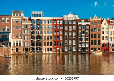 Beautiful typical Dutch dancing houses at the Amsterdam canal Damrak in sunny day, Holland, Netherlands.