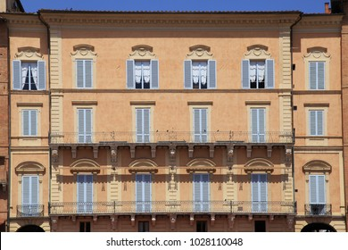 Beautiful typical red italian house with blue shutters windows, Siena, Italy
