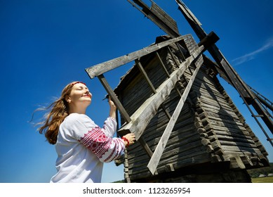 Beautiful Ukrainian girl near wooden wind mill in white ethnic shirt at national architecture museum in Pirogovo. Kiev, Ukraine