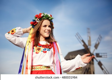 Beautiful Ukrainian girl walking in the museum of national architecture in Pirogovo in a summer day wearing national costume. Kiev, Ukraine