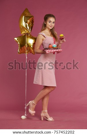 8efa5479d5c4 Beautiful Ukrainian housewife in pink dress with heels and with cupcake in  hands and gold balloons