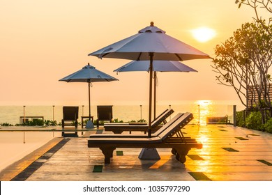 Beautiful umbrella and chair around swimming pool in hotel and resort in sunrise time