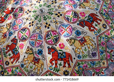 Beautiful umbrella or parasol highly decorated with intricate embroidery, mirror and bead work Jammu and Kashmir, India. Multicolored with thread designs of flowers, horse and shapes used on festivals