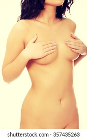 Beautiful undressed woman covering her breast.