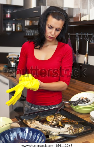 Beautiful unhappy woman preparing for cleaning  in kitchen
