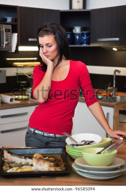 Beautiful unhappy woman standing in kitchen