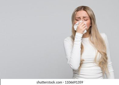 Beautiful unhealthy Caucasian female with paper napkin sneezing, experiences allergy symptoms, caught a cold, closed eyes.Sick desperate woman has flu. Rhinitis, cold, sickness, allergy concept