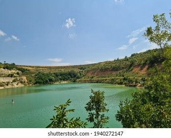 The beautiful and unique Besenovacko Lake (Lake Beli Kamen) on Fruska Gora was created in the pit of a mining mine. A lake of unique color and nature. - Shutterstock ID 1940272147