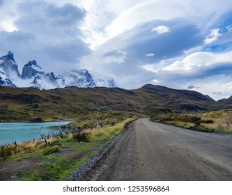 Beautiful unpaved road flanked by a lake on the way to Parque National Torres del Paine. Patagonia, Chile.