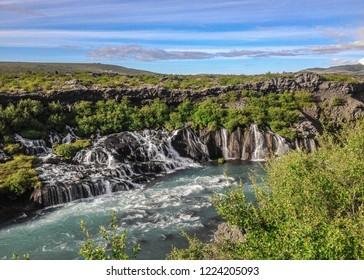 Beautiful and unusual natural phenomena – Lava falls – Hraunfossar: azur water seep through the lava and run as tiny waterfalls and rapids into Hvita River, Borgarfjordur region, West Iceland, Europe
