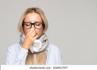 Beautiful upset young blonde woman with glasses, shirt, wrapped scarf with napkin blowing nose, closed eyes, front view/ Sick desperate female has flu/ Rhinitis, cold, sickness, allergy concept/