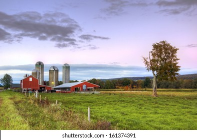 Beautiful upstate ny barn with green field in the foreground at dusk