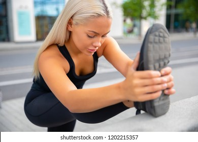 Beautiful Urban Female Stretching Her Leg Before Exercise
