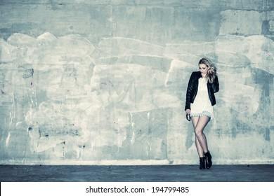 Schönes urbanes Mädchen lehnt sich an eine Betonwand, kreuz verarbeitetes Bild