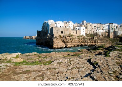 Beautiful urban landscape of Polignano a Mare overlooking the sea. Blue sky and blue sea. The waves of the sea near the shore. The white stone walls of the city. A clear Sunny day.