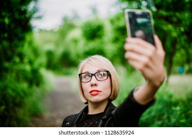 Beautiful urban woman taking picture of herself, selfie. Girl on green park background with blurred background